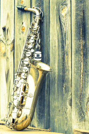 leans: Lone old saxophone leans against wooden fence outside jazz club Stock Photo