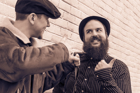 newsboy cap: Two silly enemies great through clenched teeth