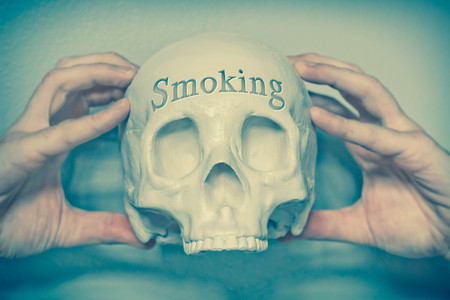 death head holding: Engraved word smoking on skull spell out cause of death