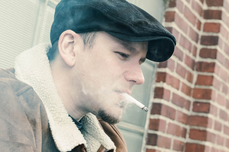 newsboy cap: Cool guy in aviator jacket and newsie cap relaxes against a glass wall and enjoys his cigarette