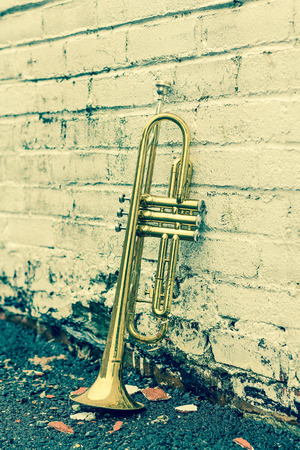 Old worn trumpet stands alone against a grungy pealing white brick wall outside a jazz club Stok Fotoğraf