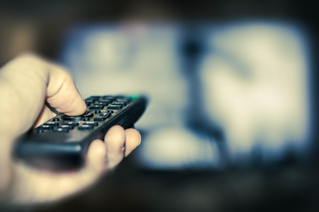 Close up of remote in hand with shallow depth of field during television watching Stock Photo