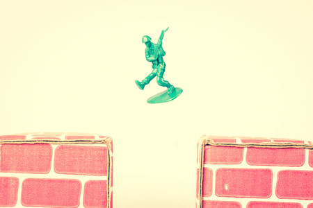 Green army men guarding the top of red cardboard brick base