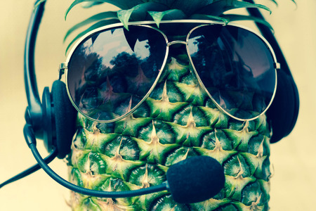 Cool pineapple with sunglasses and headset in summer themed photo