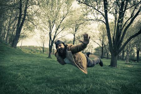 hombre con barba: Aviador barbudo eleva a través del aire como un avión