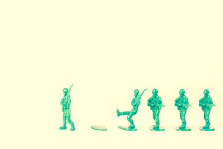 green plastic soldiers: Green army leader steps off his foot stand and others follow Stock Photo