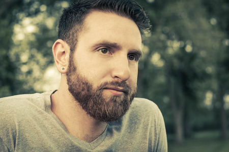 ambivalent: Portrait of bearded young man with gauged ears and stylish hair