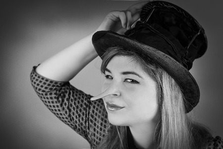 panache: Lying tramp girl wears old top hat in vintage photo style Stock Photo