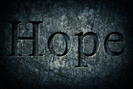 etch: Engraving spelling the word Hope on textured old surface