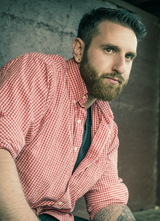 Portrait of bearded young man with gauged ears and stylish hair