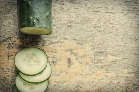 distressed: Fresh organic cucumber chopped on distressed table top Stock Photo