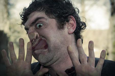 Crazy lunatic man smooshes face against glass surfaces Banco de Imagens - 48894050