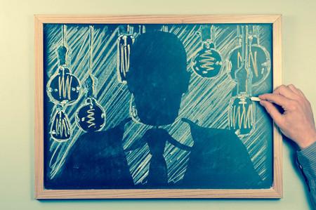 edison: Businessman surrounded by antique edison style lightbulbs drawn on chalkboard Stock Photo