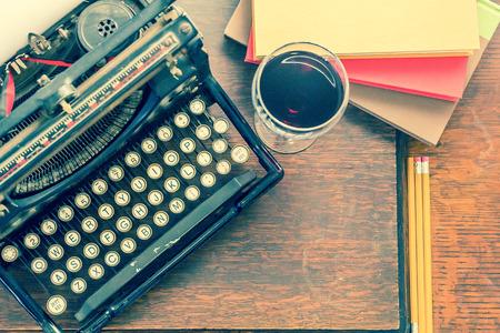 persona escribiendo: M�quina de escribir vieja de la vendimia con un vaso de vino l�pices y libros en esta escritura creativa retro y relazation tem�tica escritorio de la tapa