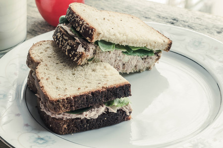 tuna salad: Whole wheat tuna salad sandwich with a glass of milk