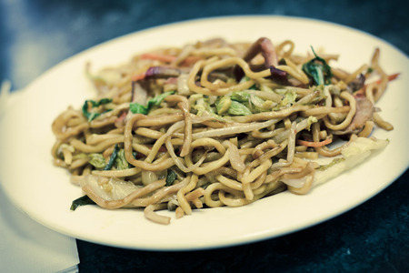 yi mein: Eating Chinese pork lo mein noodles with chopsticks