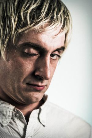 Blonde haired creepy strange man winks at the camera