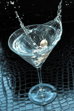 martini splash: Splashing dirty martini garnished with green olives on toothpick Stock Photo