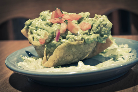 tex mex: Mexican Guacamole dip with diced tomatoes in a crunchy tortilla bowl