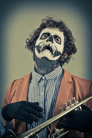 trumpet player: Crying trumpet player with face painted as human skull Stock Photo