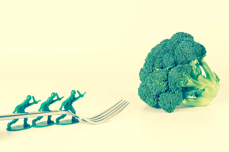 green military miniature: Army Men carry fork to broccoli in childrens healthy eating image