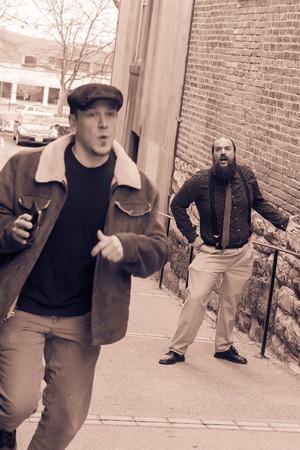 mugged: Hoodlum steals wallet from balding bearded business man Stock Photo