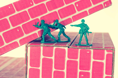 man with gun: Green army men using teamwork to make progress up the toy brick stairs
