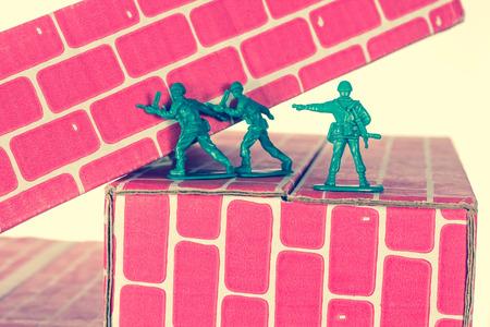 hombre rojo: Hombres verdes del ejército que utilizan el trabajo en equipo para avanzar por las escaleras de ladrillo juguete Foto de archivo
