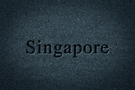 Engraving spelling the city Singapore on textured old surface Reklamní fotografie