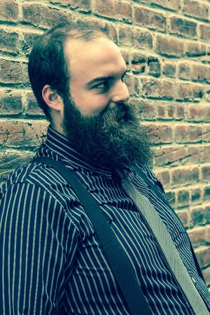 hombre con barba: Hombre barbudo Elegante mira una mirada siniestra contra el fondo de pared de ladrillo con textura
