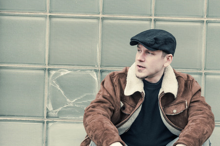 loitering: Cool guy in aviator jacket and newsie cap relaxes against a glass wall Stock Photo