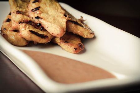Thai chicken satay skewers with spicy peanut sauce for dipping Imagens