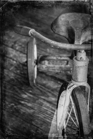 three wheeler: Antique red tricycle in vintage inspired desaturated film style photograph