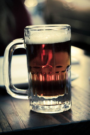 foamy: Foamy mug of cold beer dark color with lots of hops