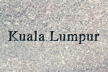 chiseled: Engraving spelling the city Kuala Lumpur on textured old surface