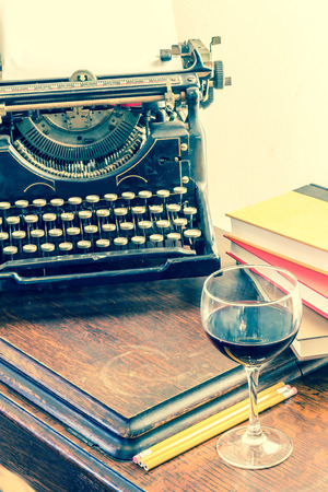writing desk: Old vintage typewriter with glass of wine pencils and books in this retro creative writing and relazation themed desk top