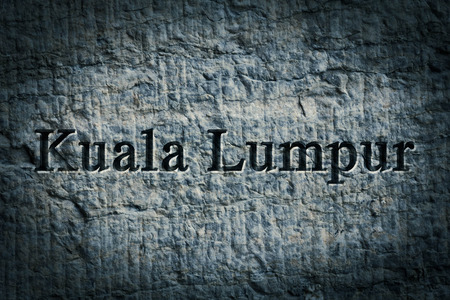Engraving spelling the city Kuala Lumpur on textured old surface
