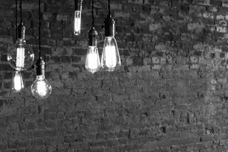 Decorative antique edison style light bulbs against brick wall background
