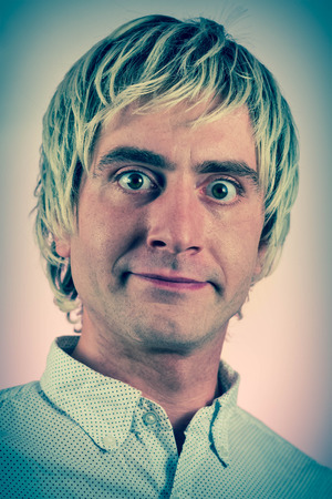 grinning: Grinning silly man with blonde hair and wide eyes Stock Photo