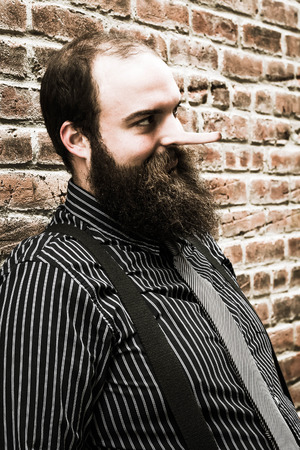 panache: Well dressed lying bearded man glares maliciously Stock Photo