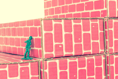 lack of confidence: Green army man banging head against a brick wall Stock Photo