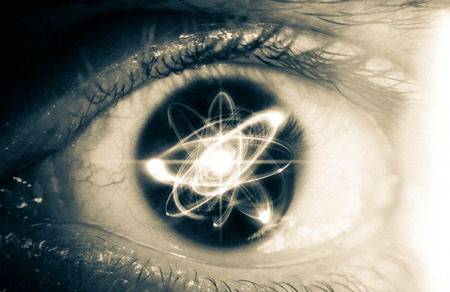 nucular: Atomic particle reflection in the pupil of an eye for physics background Stock Photo