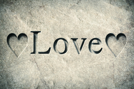 chiseled: Engraving spelling the word Love on textured old surface Stock Photo