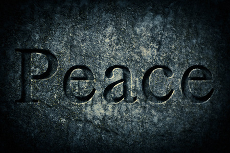 etch: Engraving spelling the word Peace on textured old surface