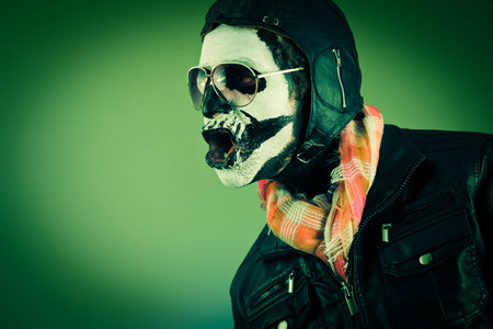 Amazed aviator with face painted as human skull