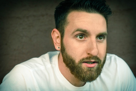eyebrow raised: Portrait of bearded young man with gauged ears and stylish hair