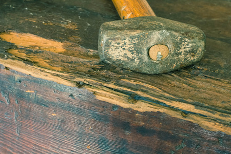 Small single handed worn sledge hammer on grunge wood background