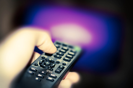 television show: Close up of remote in hand with shallow depth of field during television watching Stock Photo