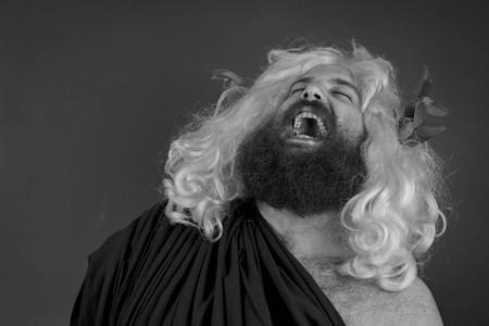 obnoxious: Laughing zeus god or jupiter against orange background Stock Photo