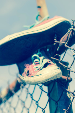 Pair of old worn classic sneakers hang from rusty chain link fence Stock Photo